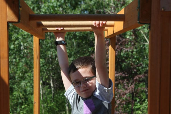 Boy enjoying hanging from the rungs of his wooden climber in the garden